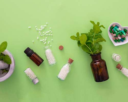 Homeopathy concept. Glass bottles and vials with homeopathic globules, liquid substance and fresh herbs, green background. Alternative herb medicine healtcare, banner